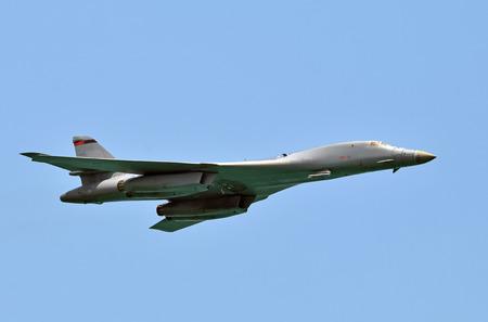 Modern strategic nuclear bomber in flight against blue sky