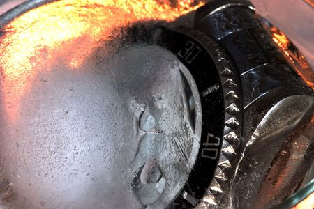 Abstract watch frozen in ice with fiery background