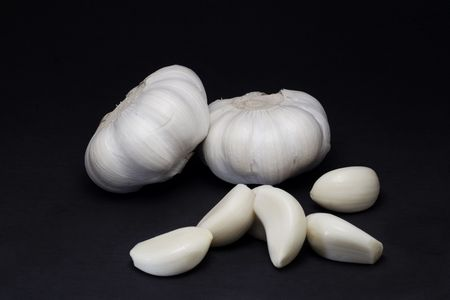 Two garlic bulbs and several cloves isolated on black background