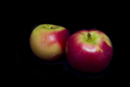 Two shiny red and green apples isolated on black background