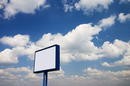 Blank billboard against blue sky with white clouds