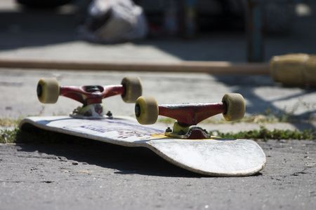 Overturned skateboard lying wheels up on the pavement Stok Fotoğraf