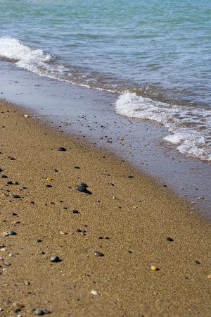 Diagonal waves breaking on sand beach Stok Fotoğraf