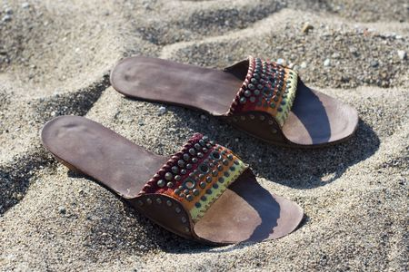 Summer lady leather slippers in beach sand