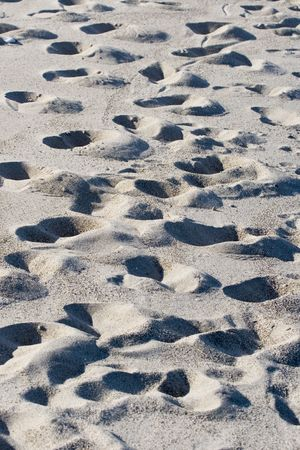 Numerous footprints imprinted in beach sand