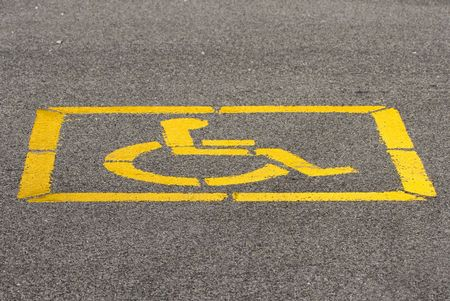 Yellow disabled sign stenciled on parking lot tarmac Stok Fotoğraf