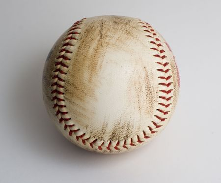 Dirty used baseball with red stitching isolated on white background