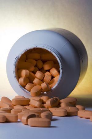 overturn: Orange pills falling out of overturned pill bottle Stock Photo