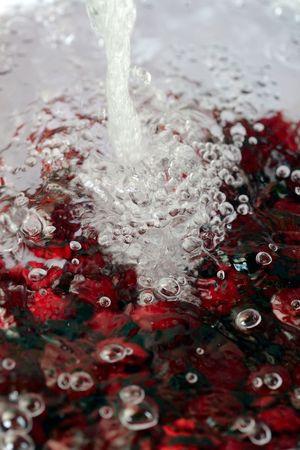 Sour cherries washed under flowing sink water Stok Fotoğraf
