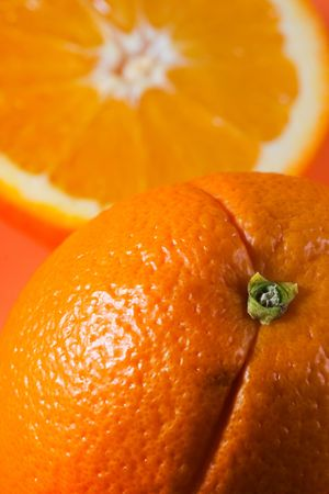 Vertical photo of whole orange in foreground with sliced orange in background Stok Fotoğraf