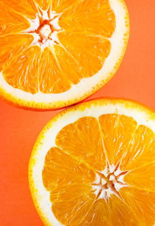 Symmetrical vertical photo of two orange slices in opposite corners of frame