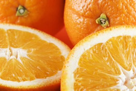 Horizontal photo of two sliced oranges in foreground and two whole oranges in background