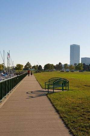 Sidewalk along marina and park with two people strolling in the distance and buildings on the horizon