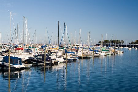 Sail boats moored diagonally in a marina, reflected in the blue water