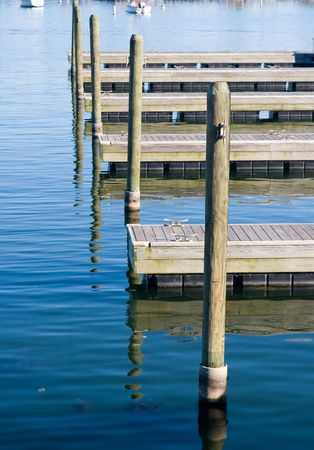 Vacant mooring piers with boat posts sticking out of the blue water Stok Fotoğraf