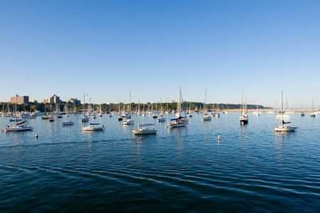 Bay with moored sail boats, blue water and azure sky