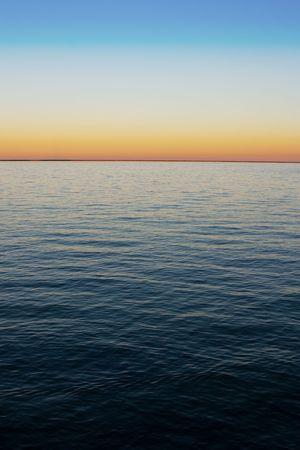 Background with dark blue water and orange-azure sky gradient at twilight