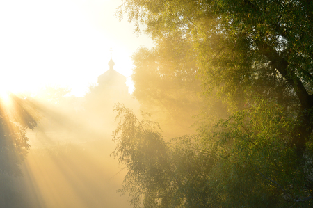 suns: misty morning and suns rays on the temple. Ukraine
