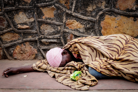 RAJGIR, INDIA - DECEMBER 4, 2016: An old man sleeps and beg tourists for money or food on the way uphill at Rajgir, India.