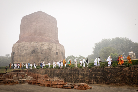 sarnath: VARANASI, INDIA - DECEMBER 2, 2016: Buddhist monks and tourists come to visit and pray in the misty morning at Dhamekh Stupa, the Buddhist historic landmark of Sarnath, Varanasi, India.