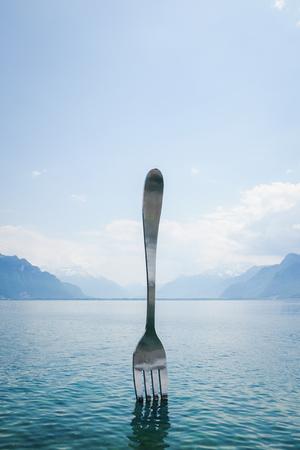vevey: VEVEY, SWITZERLAND - MAY 29, 2017: The famous giant steel fork in the water of Lake Geneva, Vevey, Switzerland. Stock Photo