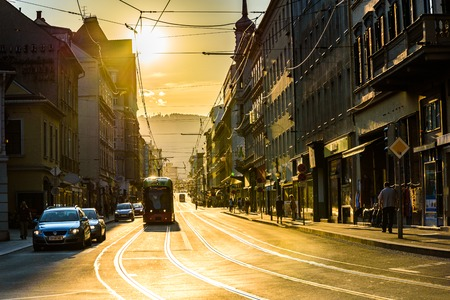 Graz city street sun setting View on a street with tram and cars