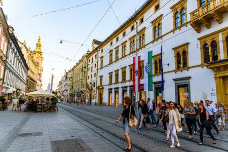Graz, Styria  Austria - 09 02 2016 : Group of people walk through tramway on herrengasse street sunny day