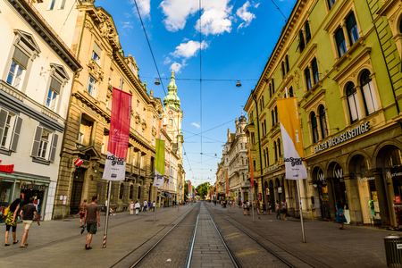 Graz, Styria  Austria - 06 19 2016 : View on Herrengasse main street in the city center, tourists walk on shopping street. Church in the background on left