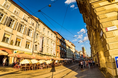 Graz, Styria  Austria - 06 19 2016 : View on Herrengasse main street in the city center, tourists walk in sunset. group people, restaurants Photo from Hauptplaz