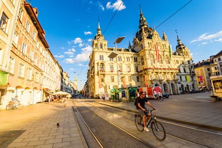 Graz, Styria / Austria - 07 09 2016 : View on Town hall on Hauptplatz city square and Herrengasse main street in the city center, bicyclist passing by on a bike, restaurants in summer sun Sajtókép