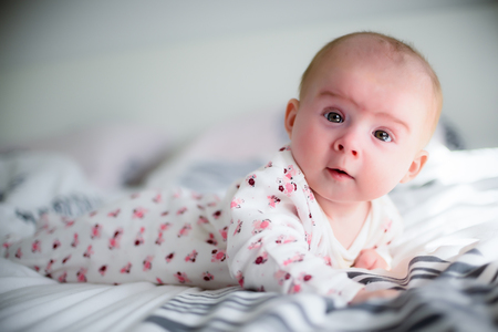 Four months old baby girl on a bed looking at camera in sunny bedroom.