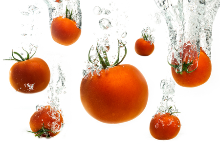Tomatoes falling into crystal clear water splashing with air bubbles. Stock Photo
