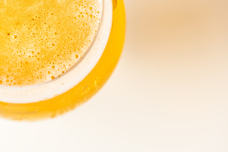 Glass of cold golden beer isolated on a white background in corner from the top view