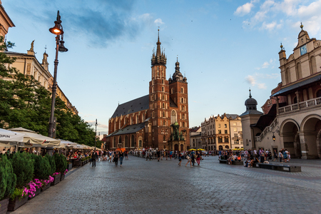 Cracow, Malopolska - Poland 25.07.2018: View at city square full of tourists walking and sitting in small restaurants in summer. Travel destination Sajtókép