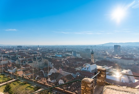 View at City Graz from Schlossberg hill, city center, clock tower, river Mur, Sun on the winter blue sky. Travel destination. Stock Photo