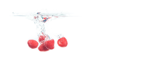 Raspberries falling into a water isolated on white background. Sinking under water with lots of air bubbles. Copy space on right