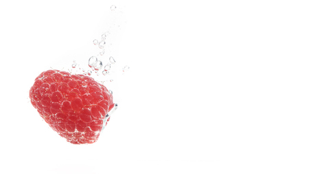 One raspberry falling into a water isolated on white background. Sinking under water with lots of air bubbles. Copy space on right