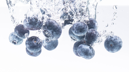 Bunch of delicious looking blueberries splashing into water surface and sinking. Isolated on white background, splash food photography. Closeup macro.