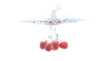 Bunch of juicy delicious looking raspberries splashing into water surface and sinking. Isolated on white background, splash food photography.