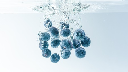 Bunch of delicious looking blueberries splashing into water surface and sinking. Isolated on white background, splash food photography. Stock Photo