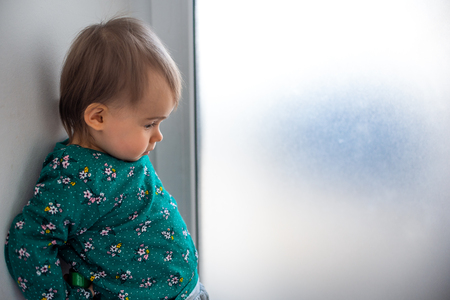 Cute caucasian one year old baby girl in green shirt standing with back against wall next to bright window. Copy space on right