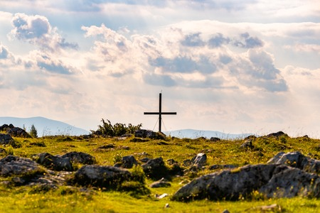 Cross on a peak of Austrian mountain Schockl in Styria Graz. Place for tourism and hiking recreation.