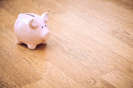 Piggy bank on an wooden floor. Light up bright. Bright white isolated background. Copy space, space for text. 免版税图像