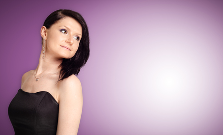 Beautiful young Brunette Girl facing empty copy space on the for text. Proposing a product, looking back. Gestures for advertisement. violet background Stock Photo