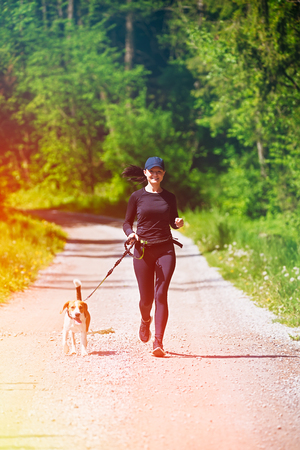 Sport girl is running with a dog (Beagle) on a leash in the spring time, sunny day on the rural road to forest. Copy space in nature