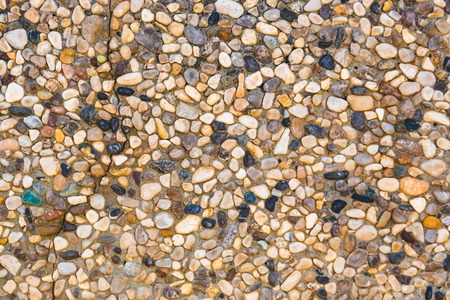 Close-up of stone wall with different pebbles. Texture, background