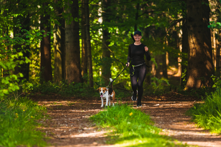 Girl is running with a dog (Beagle) on a leash in the spring time, sunny day in forest. Copy space in nature Stock Photo