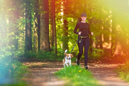 Girl is running with a dog (Beagle) on a leash in the spring time, sunny day in forest. Copy space in nature Archivio Fotografico