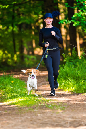 Girl is running with a dog (Beagle) on a leash in the spring time, sunny day in forest. Copy space in nature Imagens