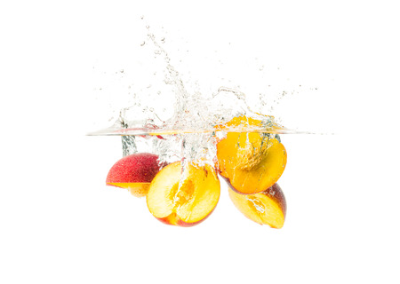 Fresh Nectarine with water splash isolated over white background. Health concept